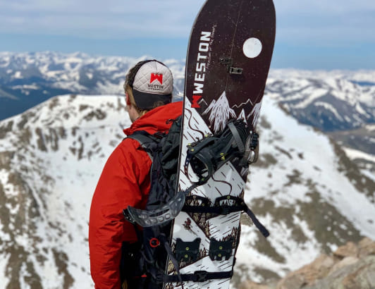 A picture of a snowboarder carrying a Weston snowboard. Weston uses Cloverly to offset carbon costs from its online store.