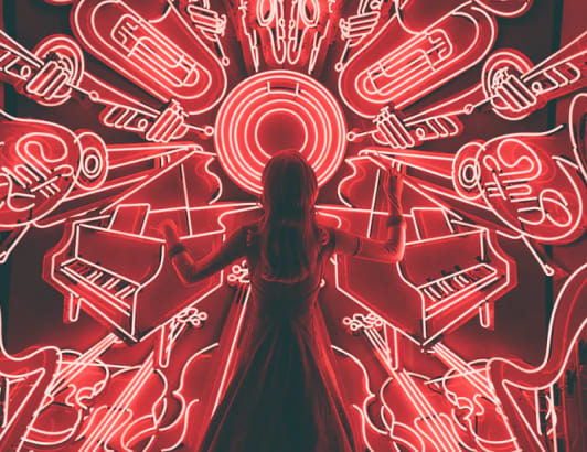 A woman standing in front of fluorescent musical instruments. Chillhop uses Cloverly for carbon offsets.
